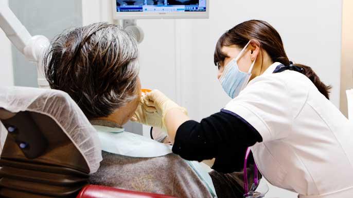 インプラント治療後のケアをしてる女性歯科医師