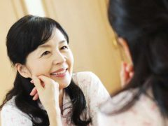 鏡で治療後のインプラントを入れた歯を見てる女性